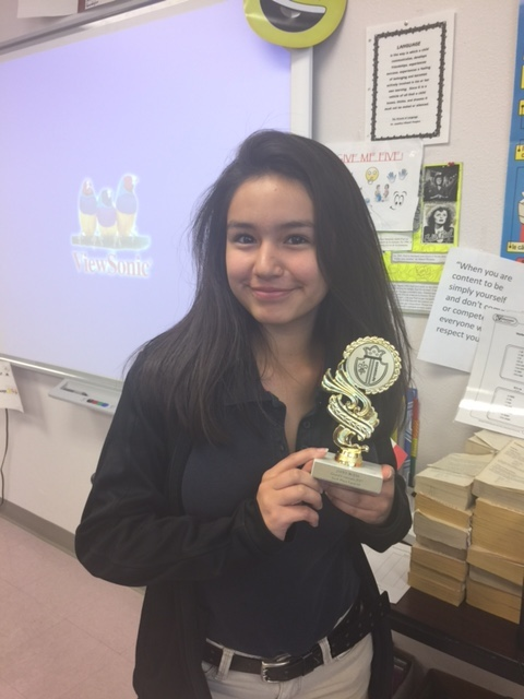 A student holds a trophy