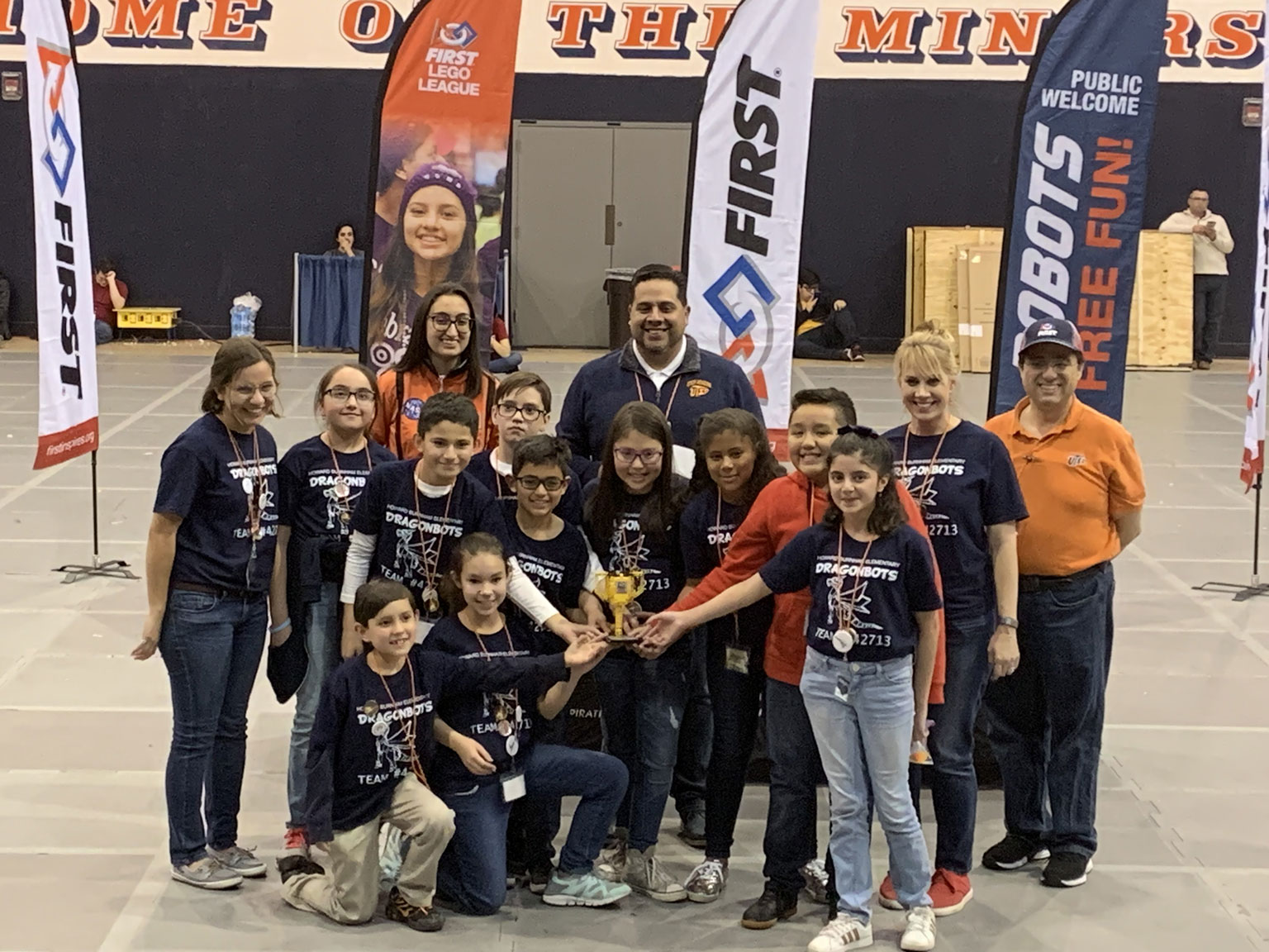 The Dragonbots team hold up their trophy. Representatives from UTEP are also present in the background.