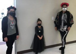 Staff (left and right) and a student (center) dressed up for the Day of the Dead